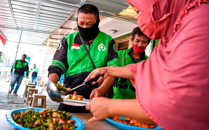 Petugas melayani pengemudi ojek daring yang akan mengambil hidangan makan siang gratis di Jalan Basuki Rahmat, Jakarta Timur, Kamis (6/8/2020). Pengelola tempat makan gratis tersebut menyediakan 100-140 porsi makan siang gratis untuk pengguna jalan dan masyarakat umum yang terdampak pandemi Covid-19 ANTARA FOTO/Nova Wahyudi