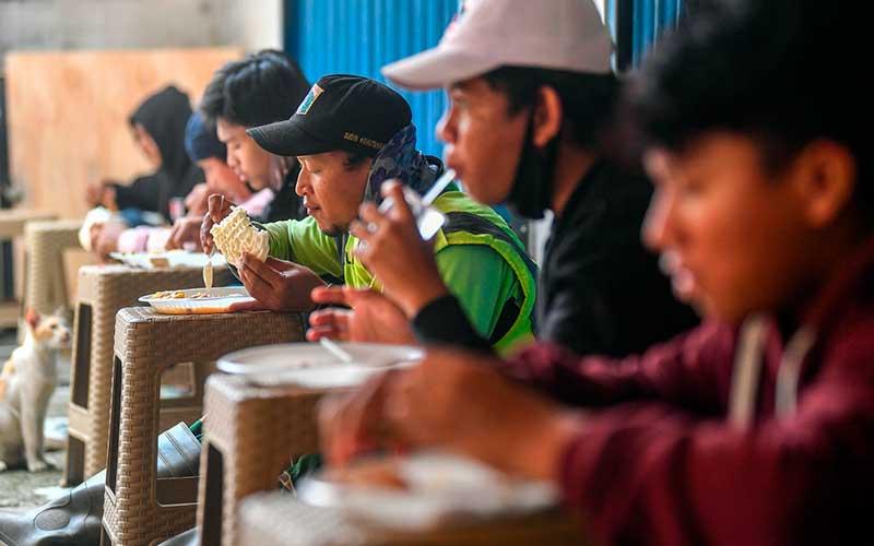 Warga menikmati makan siang gratis di Jalan Basuki Rahmat, Jakarta Timur, Kamis (6/8/2020). Pengelola tempat makan gratis tersebut menyediakan 100-140 porsi makan siang gratis untuk pengguna jalan dan masyarakat umum yang terdampak pandemi Covid-19 ANTARA FOTO/Nova Wahyudi