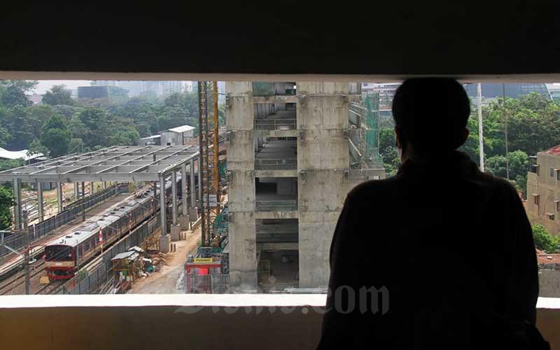 Rangkaian kereta rel listrik (KRL) melintas di sekitar proyek pembangunan apartemen berkonsep TOD di area Stasiun Pondok Cina, Depok, Jawa Barat, Sabtu (8/8/2020). Para pengembang optimistis proyek hunian yang berkonsep transit oriented development (TOD) bisa tetap diburu pencari properti di era adaptasi kebiasaan baru. Bisnis/Arief Hermawan P