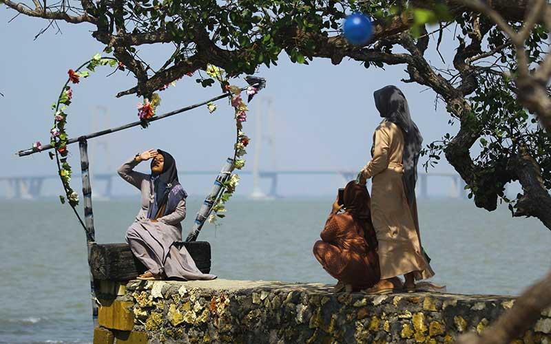 Pengunjung memotret rekannya di salah satu tempat untuk berfoto saat berwisata di Pantai Gua Petapa, Sukolilo, Bangkalan, Jawa Timur, Sabtu (8/8/2020). Obyek wisata yang menyuguhkan pemandangan pantai dan gua di Kabupaten Bangkalan tersebut mulai ramai dikunjungi wisatawan saat akhir pekan di tengah pandemi Covid-19. ANTARA FOTO/Moch Asim