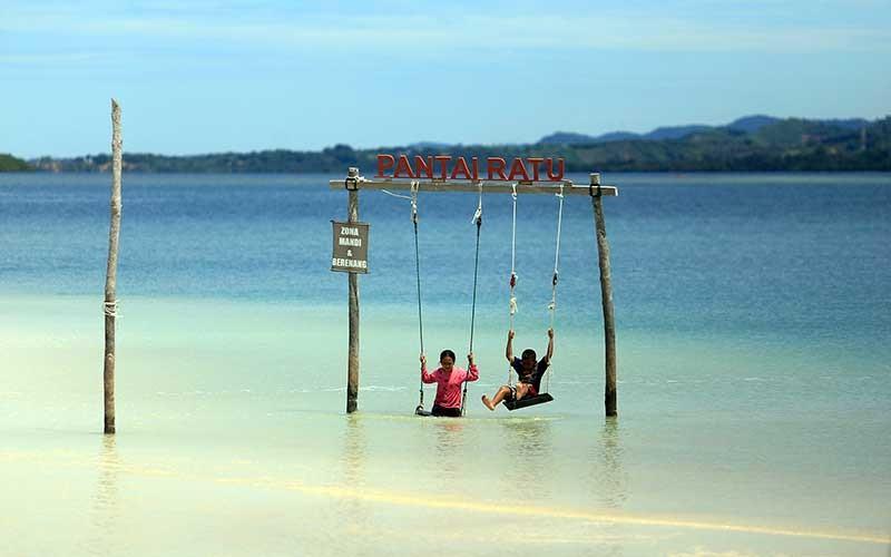 Dua bocah bermain di obyek wisata Pantai Ratu di Desa Tenilo, Kabupaten Boalemo, Gorontalo, Sabtu (8/8/2020). Obyek wisata yang dikelola oleh Badan Usaha Milik Desa (Bumdes) tersebut menawarkan panorama alam, mangrove dan pasir putih itu  merupakan destinasi wisata bahari andalan baru di daerah tersebut. ANTARA FOTO/Adiwinata Solihin