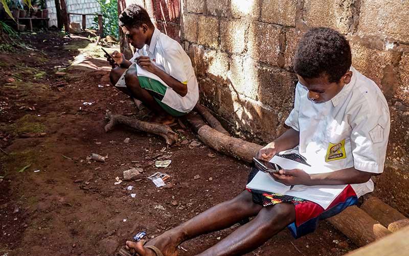 Yonas Kedeikoto (15) (kiri) dan Jekson Pigome (12) mengikuti proses belajar mengajar secara daring di Kota Jayapura, Papua, Senin (10/8/2020). Dua pelajar kelas IX dan VIII SMP Yayasan Pembinaan Pendidikan Kristen (YPPK) Kristus Raja Jayapura tersebut mengaku mulai hari ini wajib mengenakan seragam sekolah saat mengikuti pelajaran daring. ANTARA FOTO/Indrayadi TH