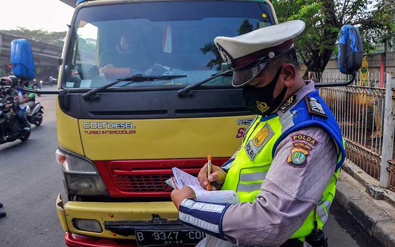 Polantas memberikan sanksi tilang kepada pengendara truk yang melanggar aturan ganjil genap di Simpang Cawang, Jakarta, Senin (10/8/2020). Direktorat Lalu Lintas Polda Metro Jaya mulai memberlakukan sanksi tilang untuk kendaraan bermotor yang melanggar sistem ganjil genap dari jam 06.10 WIB-10.00 WIB dan 16.00 WIB-21.00 WIB. ANTARA FOTO/Fakhri Hermansyah