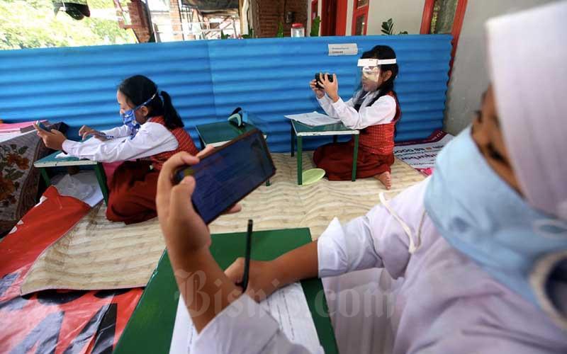 Siswa Sekolah Dasar (SD) melakukan pembelajaran jarak jauh menggunakan kuota internet secara gratis di Warung Internet Covid-19 RW 09 Kelurahan Lingkar Selatan, Bandung, Jawa Barat, Senin (10/8/2020). Bisnis/Rachman