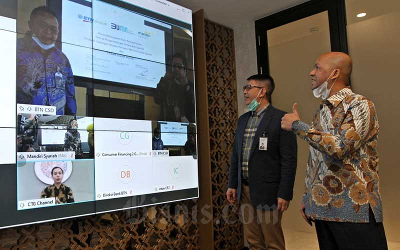 Direktur Utama Mandiri Syariah Toni EB Subari (kedua kanan) didampingi Direktur Mandiri Syariah Ade Cahyo Nugroho (kanan) menyapa Direktur Operation, IT and Digital Banking BTN Andi Nirwoto (kiri layar) dan Kepala Divisi Syariah Business Division BTN Alex Sofjan Noor (kanan layar) seusai penandatanganan Nota kesepahaman kerja sama produk keuangan syariah yang dilakukan secara virtual di Jakarta, Selasa (11/8/2020). Bisnis/Arief Hermawan P