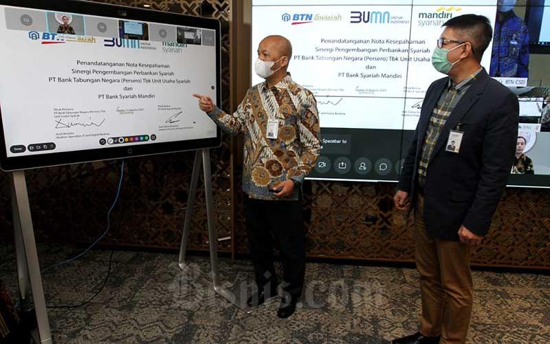Direktur Mandiri Syariah Ade Cahyo Nugroho (kiri) disaksikan Direktur Utama Mandiri Syariah Toni EB Subari menandatangani perjanjian kerja sama dengan Unit Usaha Syariah BTN yang dilakukan secara virtual di Jakarta, Selasa (11/8/2020). Bisnis/Arief Hermawan P