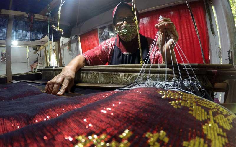 Pekerja dari Songket Aina, melakukan proses pembuatan benang lungsi untuk kebutuhan tenun, di Silungkang, Kota Sawahlunto, Sumatera Barat, Selasa (11/8/2020). Industri tenun Silungkang yang masih dilakukan secara tradisional tersebut, kembali berproduksi untuk memenuhi pesanan dari berbagai daerah, setelah berhenti akibat pandemi Covid-19. ANTARA FOTO/Iggoy el Fitra