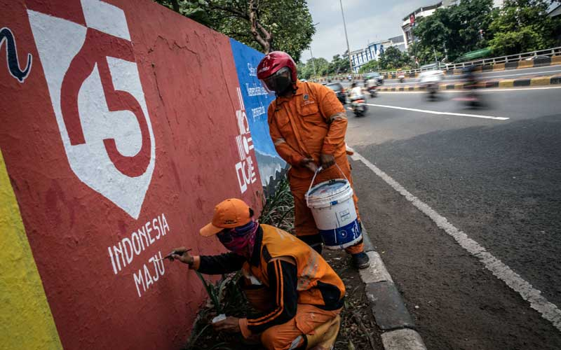 Dua Petugas Prasarana dan Sarana Umum (PPSU) menyelesaikan pembuatan mural bertemakan HUT Ke-75 Kemerdekaan RI,  di kawasan Tebet, Jakarta, Selasa (11/8/2020). Pemerintah mengangkat tema Indonesia Maju sebagai simbolisasi Indonesia yang mampu memperkokoh kedaulatan, persatuan, dan kesatuan Indonesia. ANTARA FOTO/Aprillio Akbar