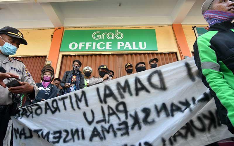Sejumlah pengemudi ojek daring menyegel kantor Grab Palu saat unjuk rasa di Palu, Sulawesi Tengah, Rabu (12/8/2020). Mereka memprotes perubahan skema dan nilai insentif yang dinilai memberatkan pengemudi terutama ditengah pandemi Covid-19 serta meminta manajemen untuk menerapkan sistem yang menguntungkan kedua belah pihak. ANTARA FOTO/Mohamad Hamzah