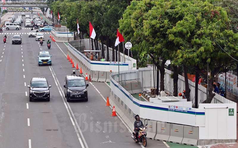 Sejumlah kendaraan melintas di samping lokasi proyek pembangunan MRT fase 2A di Jalan MH Thamrin, Jakarta, Rabu (12/8/2020). Dirut PT MRT Jakarta William P Sabandar mengatakan proyek MRT fase 2A merupakan bagian dari pemulihan ekonomi, pada tahun ini pengerjaan proyek MRT Jakarta bakal menyerap anggaran Rp 1,5 triliun. Bisnis/Eusebio Chrysnamurti