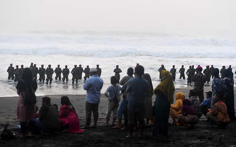 Sejumlah keluarga Prajurit Marinir menyaksikan prosesi upacara Pembaretan Prajurit Korps Marinir di Pantai Baruna Kondang Iwak, Malang, Jawa Timur, Rabu (12/8/2020). ANTARA FOTO/Zabur Karuru