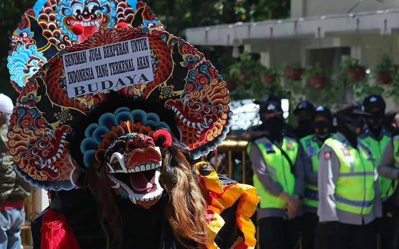 Warga dari Aliansi Pekerja Seni Surabaya menampilkan kesenian 'Barongan' saat berunjuk rasa di Surabaya, Jawa Timur, Rabu (12/8/2020). Massa aksi mendesak Pemkot Surabaya memberikan izin digelarnya kegiatan acara kesenian, hajatan maupun kegiatan lainnya agar mereka dapat kembali menjalankan profesinya. ANTARA FOTO/Didik Suhartono