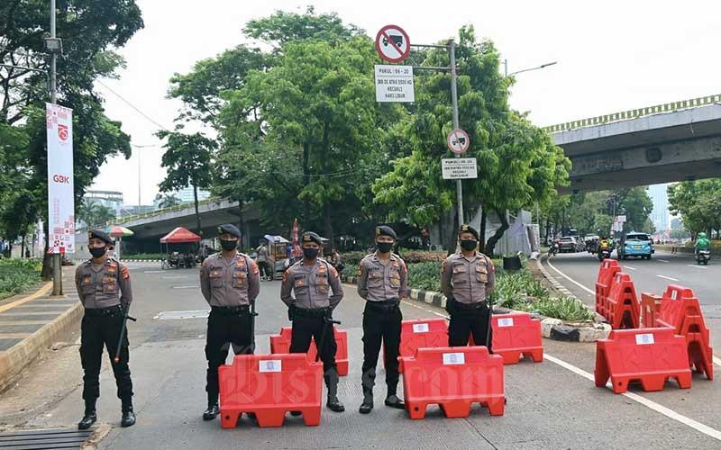 Petugas kepolisian berjaga saat melakukan pengamanan Sidang Tahunan MPR RI 2020 di Jalan Gerbang Pemuda, Senayan, Jakarta, Jumat (14/8/2020). Bisnis/Eusebio Chrysnamurti