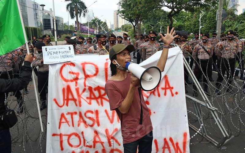 Sejumlah mahasiswa dari berbagai kampus melakukan aksi unjuk rasa di Jalan Gerbang Pemuda, Senayan, Jakarta, Jumat (14/8/2020). Aksi yang dilakukan bertepatan dengan Sidang Tahunan MPR itu dilakukan untuk menolak rencana pengesahaan RUU Omnibus Law Cipta Lapangan Kerja. Bisnis/Eusebio Chrysnamurti