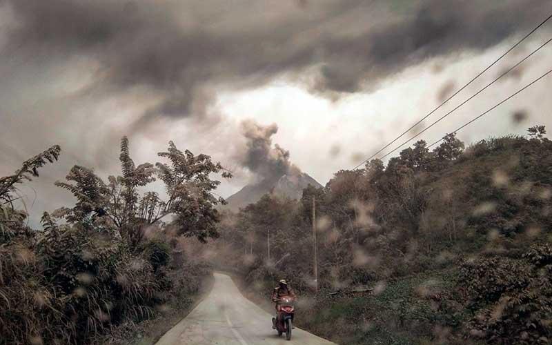 Pengendara melintas di jalan dengan latar belakang Gunung Sinabung yang menyemburkan material vulkanik di Desa Suka Tepu, Karo, Sumatera Utara, Jumat (14/8/2020). ANTARA FOTO/Tibta Peranginangin