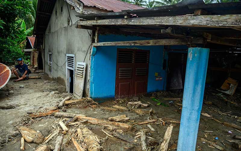 Warga berada di dekat rumahnya yang tertimbun lumpur akibat banjir bandang di Desa Rogo, Kecamatan Dolo Selatan, Kabupaten Sigi, Sulawesi Tengah, Selasa (15/9/2020). Banjir bandang yang terjadi pada Senin (14/9/2020) malam karena hujan lebat itu mengakibatkan sedikitnya 15 rumah warga rusak berat dan puluhan lainnya rusak ringan dan digenangi lumpur. Sebanyak 59 Kepala Keluarga atau atau 224 jiwa terpaksa mengungsi ke tempat aman. ANTARA FOTO/Basri Marzuki