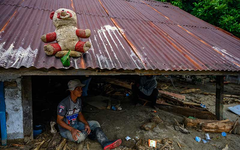 Warga berada di rumahnya yang tertimbun lumpur akibat banjir bandang di Desa Rogo, Kecamatan Dolo Selatan, Kabupaten Sigi, Sulawesi Tengah, Selasa (15/9/2020). Banjir bandang yang terjadi pada Senin (14/9/2020) malam karena hujan lebat itu mengakibatkan sedikitnya 15 rumah warga rusak berat dan puluhan lainnya rusak ringan dan digenangi lumpur. Sebanyak 59 Kepala Keluarga atau atau 224 jiwa terpaksa mengungsi ke tempat aman. ANTARA FOTO/Basri Marzuki