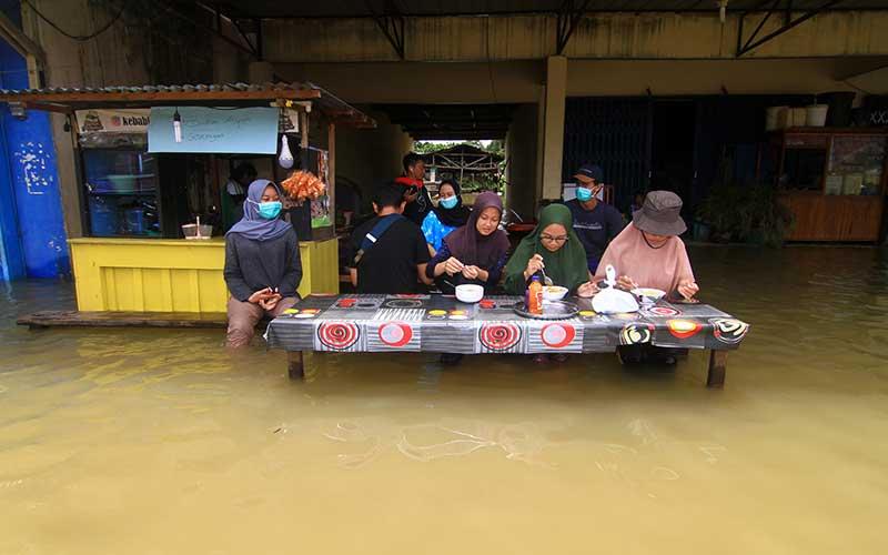 Sejumlah warga menyantap makanan di sebuah warung yang terendam banjir di Putussibau, Kabupaten Kapuas Hulu, Kalimantan Barat, Selasa (15/9/2020). Banjir setinggi 1-5 meter yang melanda Putussibau sejak Minggu (13/9/2020) hingga Selasa (15/9/2020) melumpuhkan aktivitas masyarakat di kota tersebut. ANTARA FOTO/Jessica Helena Wuysang