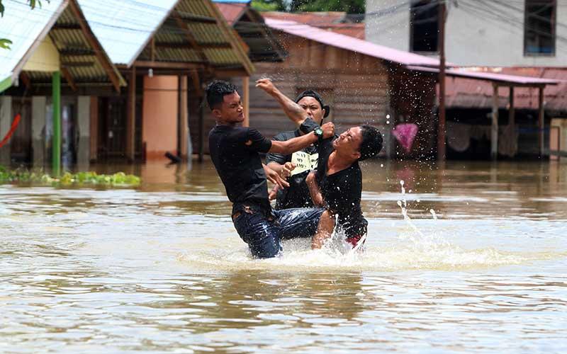 Dua pemuda terlibat adu pukul karena berselisih paham di pemukiman yang terendam banjir di Putussibau, Kabupaten Kapuas Hulu, Kalimantan Barat, Selasa (15/9/2020). Banjir setinggi 1-5 meter yang melanda Putussibau sejak Minggu (13/9/2020) hingga Selasa (15/9/2020) melumpuhkan aktivitas masyarakat di kota tersebut. ANTARA FOTO/Jessica Helena Wuysang