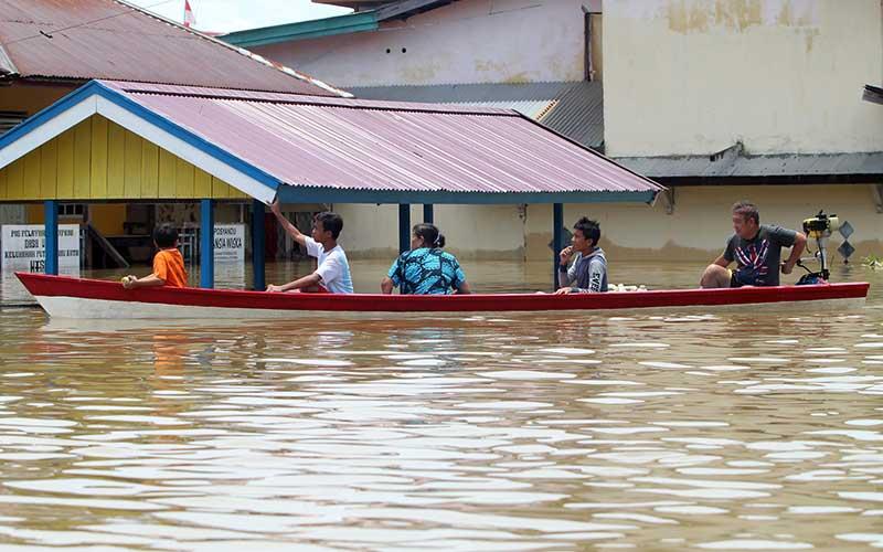 Sejumlah warga menggunakan perahu saat melintasi kawasan perkantoran yang terendam banjir di Putussibau, Kabupaten Kapuas Hulu, Kalimantan Barat, Selasa (15/9/2020). Banjir setinggi 1-5 meter yang melanda Putussibau sejak Minggu (13/9/2020) hingga Selasa (15/9/2020) melumpuhkan aktivitas masyarakat di kota tersebut. ANTARA FOTO/Jessica Helena Wuysang