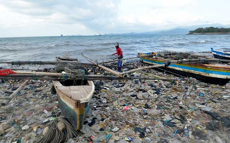 Nelayan menyiapkan jaring untuk menangkap ikan di pantai Sukaraja Bandar Lampung, Lampung, Rabu (16/9/2020). Menurut warga dan nelayan sekitar, sampah yang menumpuk menutupi pesisir pantai itu sebagiam besar berasal dari limbah rumah tangga dan plastik yang terseret arus dan kian menumpuk sehingga mencemari kawasan pantai tersebut. ANTARA FOTO/Ardiansyah