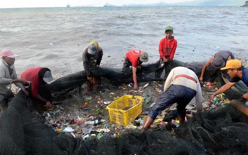 Nelayan memilih ikan hasil tangkapan yang bercampur dengan sampah yang masuk ke dalam jaring di pantai Sukaraja Bandar Lampung, Lampung, Rabu (16/9/2020). Menurut warga dan nelayan sekitar, sampah yang menumpuk menutupi pesisir pantai itu sebagiam besar berasal dari limbah rumah tangga dan plastik yang terseret arus dan kian menumpuk sehingga mencemari kawasan pantai tersebut. ANTARA FOTO/Ardiansyah