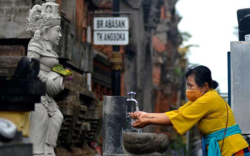 Umat Hindu mencuci tangan saat akan bersembahyang Hari Raya Galungan di Pura Jagatnatha, Denpasar, Bali, Rabu (16/9/2020). ANTARA FOTO/Fikri Yusuf