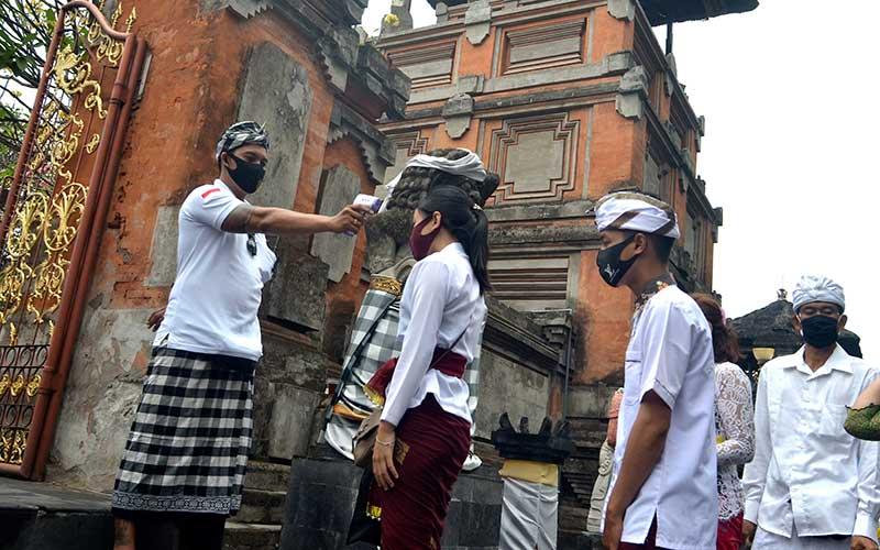 Pecalang atau petugas pengamanan adat Bali memeriksa suhu tubuh umat Hindu yang akan bersembahyang saat Hari Raya Galungan di Pura Jagatnatha, Denpasar, Bali, Rabu (16/9/2020). ANTARA FOTO/Fikri Yusuf