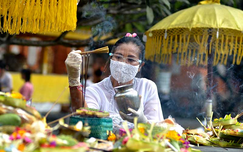 Pemuka agama Hindu memercikkan air suci saat persembahyangan Hari Raya Galungan di Pura Jagatnatha, Denpasar, Bali, Rabu (16/9/2020). ANTARA FOTO/Fikri Yusuf
