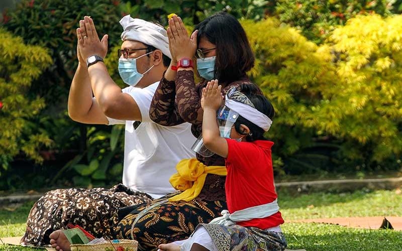 Umat Hindu beribadah saat merayakan hari raya Galungan di Pura Amerta Jati, Jakarta Selatan, Rabu (16/9/2020). Persembayangan Hari Raya Galungan dilakukan di tengah pandemi Covid-19 dengan menerapkan protokol kesehatan menggunakan masker dan menjaga jarak. ANTARA FOTO/Asprilla Dwi Adha