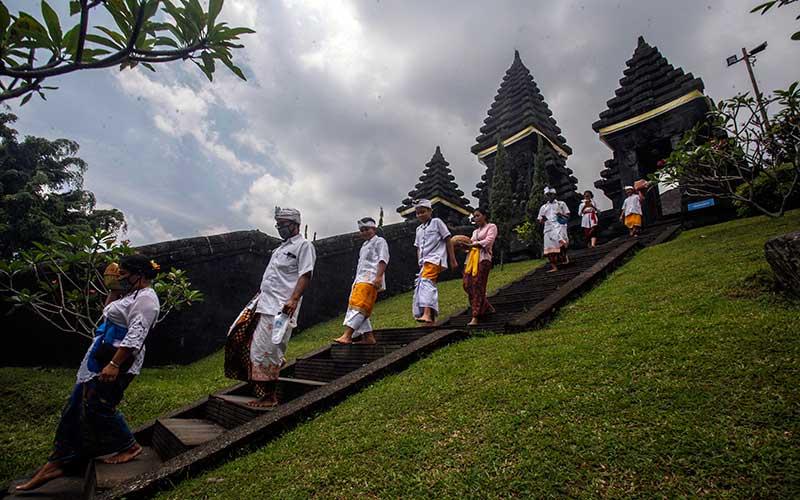 Umat Hindu berjalan menuruni pura setelah melakukan  persembahyangan bersama Hari Raya Galungan di  Pura Parahyangan Agung Jagatkarta, Taman Sari, Kabupaten Bogor, Jawa Barat, Rabu (16/9/2020). Hari Raya Galungan merupakan hari kemenangan kebenaran (Dharma) atas kejahatan (Adharma) yang dirayakan umat Hindu setiap enam bulan sekali dengan melakukan persembahyangan di tiap-tiap Pura. ANTARA FOTO/Yulius Satria Wijaya