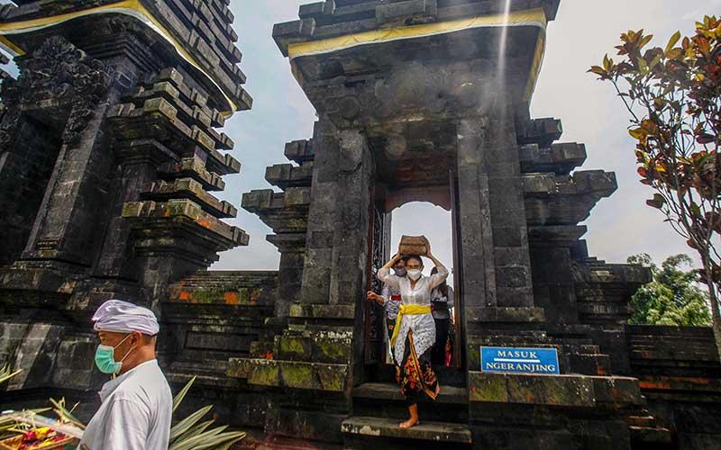 Umat Hindu membawa sesaji sebelum melakukan  persembahyangan bersama Hari Raya Galungan di  Pura Parahyangan Agung Jagatkarta, Taman Sari, Kabupaten Bogor, Jawa Barat, Rabu (16/9/2020). Hari Raya Galungan merupakan hari kemenangan kebenaran (Dharma) atas kejahatan (Adharma) yang dirayakan umat Hindu setiap enam bulan sekali dengan melakukan persembahyangan di tiap-tiap Pura. ANTARA FOTO/Yulius Satria Wijaya