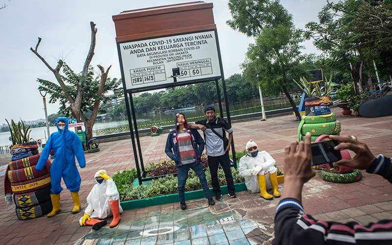 Warga berfoto dengan karya instalasi waspada Covid-19 di Danau Sunter Selatan yang ditutup di Jakarta, Rabu (16/9/2020). Pemprov DKI Jakarta kembali menutup kawasan tersebut untuk pengunjung seiring pemberlakuan Pembatasan Sosial Berskala Besar (PSBB) Jakarta untuk mencegah penyebaran Covid-19. ANTARA FOTO/Aprillio Akbar