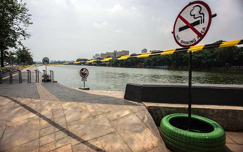 Garis pembatas larangan masuk terpasang di Danau Sunter Selatan, Jakarta, Rabu (16/9/2020). Pemprov DKI Jakarta kembali menutup kawasan tersebut untuk pengunjung seiring pemberlakuan Pembatasan Sosial Berskala Besar (PSBB) Jakarta untuk mencegah penyebaran Covid-19. ANTARA FOTO/Aprillio Akbar