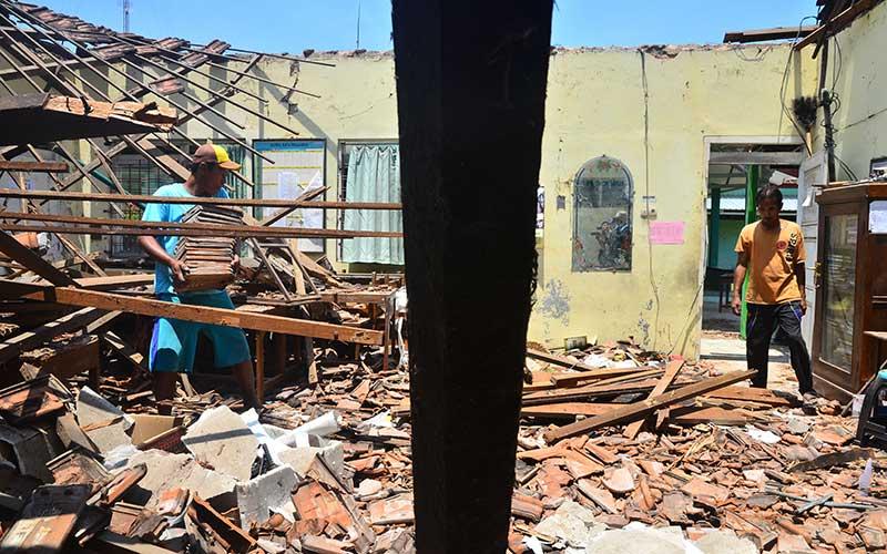 Pekerja membersihkan sisa material bangunan atap Sekolah Dasar 4 Loram Wetan yang roboh di Kudus, Jawa Tengah, Rabu (16/9/2020). Atap bangunan gudang dan ruang UKS di sekolah itu roboh karena kondisi kayu yang sudah rapuh. ANTARA FOTO/Yusuf Nugroho
