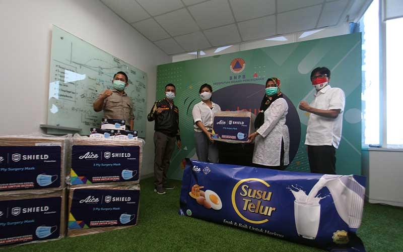 Brand Manager Aice Group Sylvana Zhong (tengah) bersama Direktur Kesiapsiagaan BNPB Eny Supartini (kedua kanan) didampingi JKMC Jaringan Katholik Melawan Covid Yulius Setiarto (kiri), Ketua Gugus Tugas Penanganan Covid GP Ansor Faisal Saimima (dua kiri) dan Direktur Peringatan Dini BNPB Afrial Rosya (kanan) saat acara penyerahan donasi berupa masker melalui BNPB di Jakarta, Rabu (16/9/2020). Bisnis