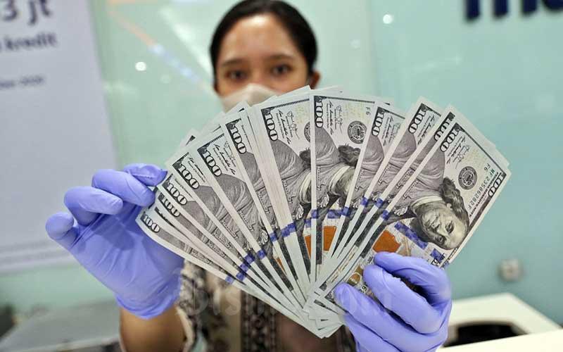 Karyawati menghitung uang dolar AS di Jakarta, Rabu (16/9/2020). Nilai tukar rupiah di pasar spot ditutup melemah 2 poin atau 0,01 persen ke level Rp 14.843 per dolar AS pada akhir perdagangan Rabu (16/9/2020). Bisnis/Eusebio Chrysnamurti