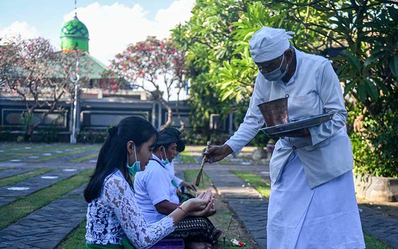 Pemuka agama Hindu memercikkan air suci saat persembahyangan Hari Raya Galungan di Pura Agung Jagat Karana Surabaya, Jawa Timur, Rabu (16/9/2020). Hari Raya Galungan merupakan hari kemenangan kebenaran (Dharma) atas kejahatan (Adharma) yang dirayakan umat Hindu setiap enam bulan sekali dengan melakukan persembahyangan di tiap-tiap Pura. ANTARA FOTO/M Risyal Hidayat