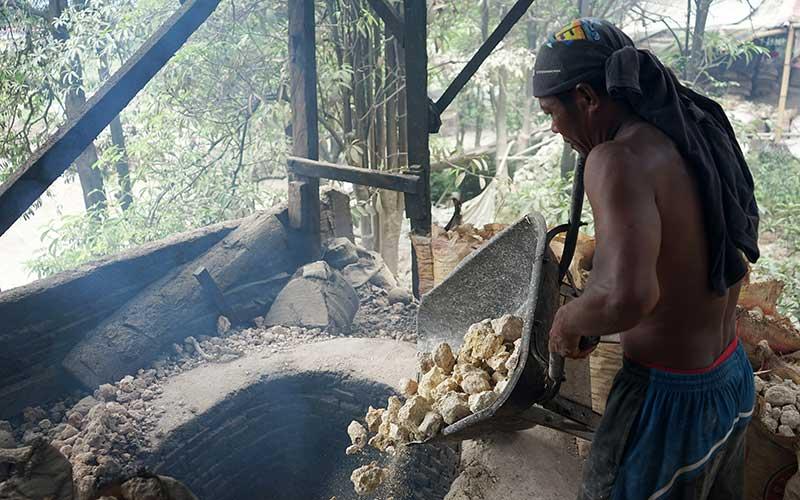 Seorang pekerja memasukkan batu kapur yang telah dipecahkan ke dalam lubang pembakaran di Buliide, Kota Gorontalo, Gorontalo, Rabu (16/9/2020). Batu kapur yang biasa di gunakan untuk bahan bangunan itu dijual dengan harga Rp12.500 per 12 kg dan Rp15.000 per 16 kg yang dipasarkan ke sejumlah daerah di Sulawesi. ANTARA FOTO/Adiwinata Solihin