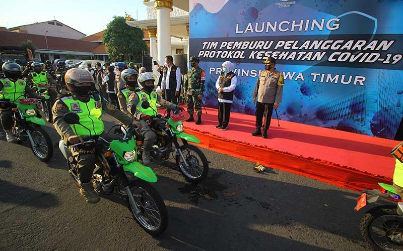 Gubernur Jawa Timur Khofifah Indar Parawansa (kedua kanan), Pangdam V/Brawijaya Mayjen TNI Widodo Iryansyah (ketiga kanan) dan Kapolda Jawa Timur Irjen Pol M Fadil Imran (kanan) melepaskan tim pemburu pelanggaran protokol kesehatan Covid-19 saat diluncurkan di Gedung Negara Grahadi, Surabaya, Jawa Timur, Rabu (16/9/2020). ANTARA FOTO/Moch Asim