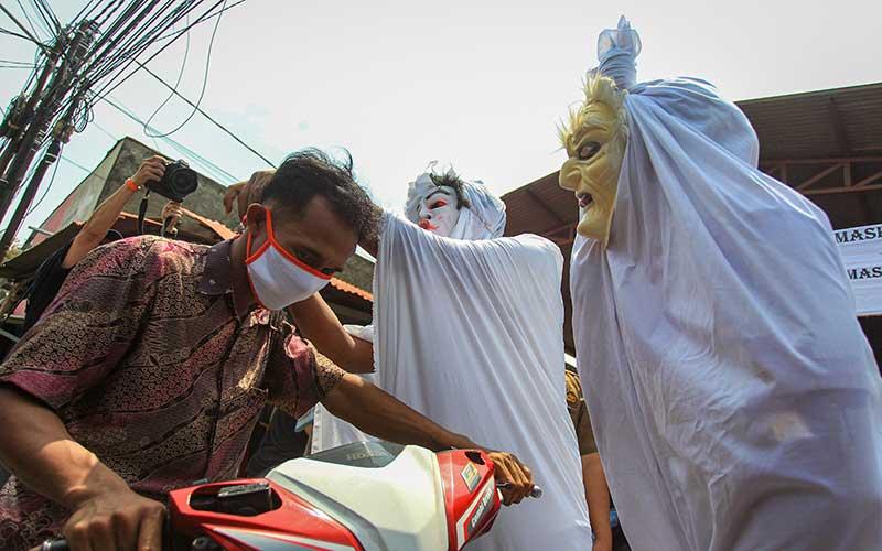 Petugas Satpol PP Kecamatan Larangan mensosialisasikan penggunaan masker dengan menggunakan kostum hantu pocong di Pasar Kreo, Kota Tangerang, Banten, Rabu (16/9/2020). Kegiatan tersebut bertujuan sebagai pengingat masyarakat untuk selalu mematuhi protokol kesehatan guna menghindari penyebaran Covid-19 ANTARA FOTO/Fauzan