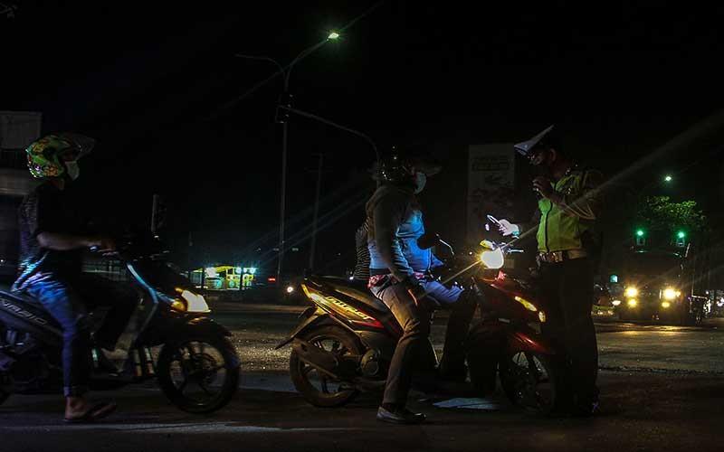 Petugas Satlantas Polresta Pekanbaru memeriksa identitas kependudukan warga yang hendak melintas ketika penerepan jam malam Pembatasan Sosial Berskala Mikro (PSBM) di Kecamatan Tampan Pekanbaru, Riau, Rabu (16/9/2020) malam. Pemerintah Kota Pekanbaru menerapkan PSBM dan penerapan jam malam dari pukul 21.00 hingga 07.00 WIB sampai 28 September 2020 guna menekan angka penyebaran Covid-19 di wilayah tersebut. ANTARA FOTO/Rony Muharrman