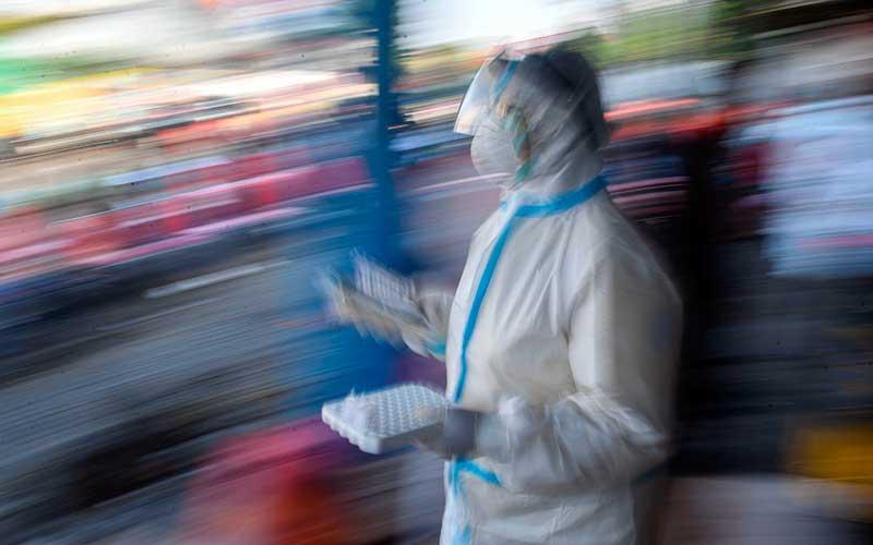 Seorang tenaga kesehatan yang mengenakan alat pelindung diri lengkap membawa sample tes usap (swab test) Covid-19 milik warga di kawasan Pasar Keputran, Surabaya, Jawa Timur, Kamis (17/9/2020). Pemerintah Kota Surabaya menyediakan 500 kuota tes usap secara gratis bagi warga Surabaya yang melintas di kawasan tersebut. ANTARA FOTO/M Risyal Hidayat