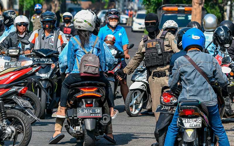 Petugas Satuan Polisi Pamong Praja (Satpol PP) mengarahkan pengendara sepeda motor untuk mengikuti tes usap (swab test) Covid-19 di kawasan Pasar Keputran, Surabaya, Jawa Timur, Kamis (17/9/2020). Pemerintah Kota Surabaya menyediakan 500 kuota tes usap secara gratis bagi warga Surabaya yang melintas di kawasan tersebut. ANTARA FOTO/M Risyal Hidaya