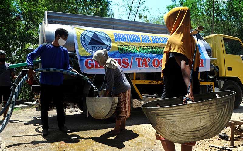 Relawan memasukkan air ke dalam timba saat pendistribusian air bersih di Desa Pamoroh, Pamekasan, Jawa Timur, Kamis (17/9/2020). Distribusi air bersih yang disalurkan oleh Forum Relawan Penanggulangan Bencana (FRPB) tersebut guna membantu warga yang terdampak kekeringan akibat musim kemarau. ANTARA FOTO/Saiful Bahri