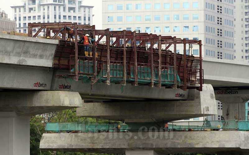 Pekerja menyelesaikan pembangunan jalur kereta Lintas Rel Terpadu (LRT) Jabodebek di Jakarta, Minggu (20/9/2020). PT Kereta Api Indonesia (KAI) selaku penyelenggara sarana dan prasarana proyek LRT Jabodebek menyampaikan guna mengakomodir kebutuhan mobilisasi masyarakat, disediakan 18 stasiun pemberhentian. Bisnis/Himawan L Nugraha