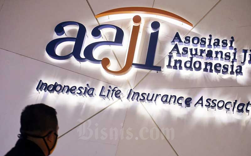 Karyawan melintas di depan logo asuransi jiwa di Jakarta, Senin (21/9/2020). Berdasarkan Statistik Asuransi Otoritas Jasa Keuangan (OJK), perolehan premi pada Juni 2020 tercatat senilai Rp15,41 triliun. Perolehan premi bulanan itu merupakan yang tertinggi pada tahun ini dan berhasil tumbuh dari titik terendah pada April 2020 senilai Rp11,19 triliun. Bisnis/Abdurachman