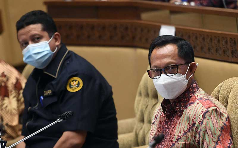 Mendagri Tito Karnavian (kanan) dan Ketua Dewan Kehormatan Penyelenggara Pemilu (DKPP) Muhammad (kiri) mengikuti rapat kerja dengan Komisi II DPR di Kompleks Parlemen, Senayan, Jakarta, Senin (21/9/2020). DPR menyetujui pagu anggaran Kementerian Dalam Negeri untuk tahun 2021 sebesar Rp3,2 triliun dan menyetujui tambahan anggaran sebesar Rp1,2 triliun untuk dibahas di Badan Anggaran DPR. ANTARA FOTO/Akbar Nugroho Gumay