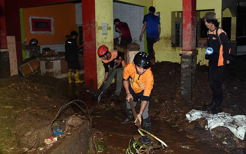 Petugas membersihkan endapan lumpur di lokasi terdampak banjir bandang di Desa Mekarsari, Kecamatan Cicurug, Kabupaten Sukabumi, Jawa Barat, Senin (21/9/2020). Banjir bandang karena hujan deras tersebut mengakibatkan satu rumah warga terseret arus dan dua orang dilaporkan hilang terbawa arus. ANTARA FOTO/Iman Firmansyah
