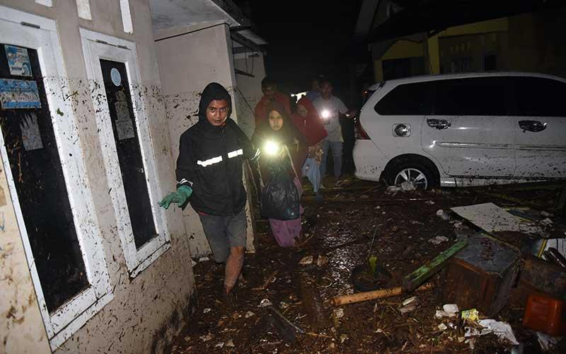 Warga melintasi genangan banjir bandang di Desa Mekarsari, Kecamatan Cicurug, Kabupaten Sukabumi, Jawa Barat, Senin (21/9/2020). Pada pukul 20.30, Pusat Pengendali Operasi (Pusdalops) BNPB mencatat sebanyak 12 rumah hanyut, 85 rumah terendam dan 1 unit mobil tersapu saat banjir bandang. ANTARA FOTO/Iman Firmansyah